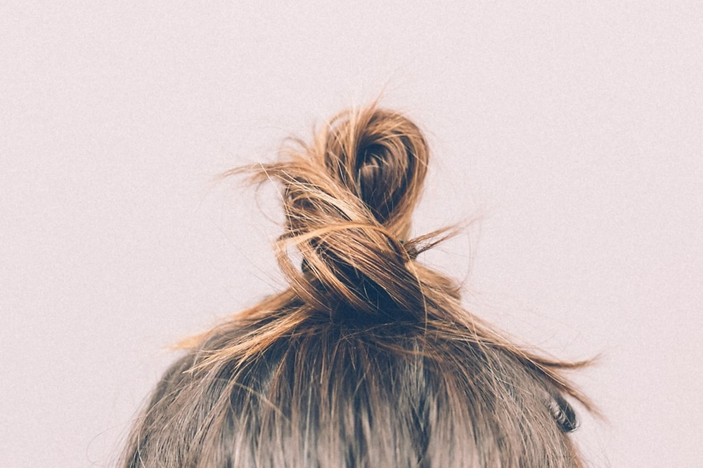 Blond-brown hair pulled into a messy topknot.