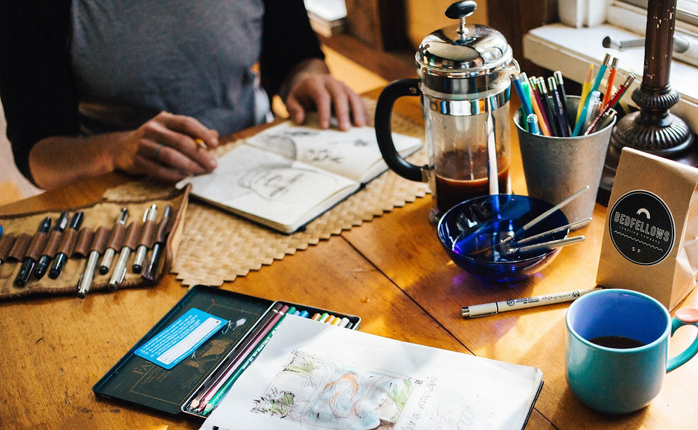 Torso of person at wooden table with an open sketchpad in front of them, a variety of pens, and a pot of coffee.
