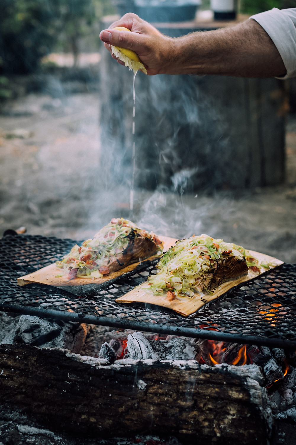 Chef squeezes lemon onto two orders of fish being smoked outdoors on cedar.