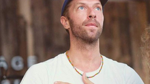 Chris Martin wearing a Love Button Cap designed by Red Cloud Agency.