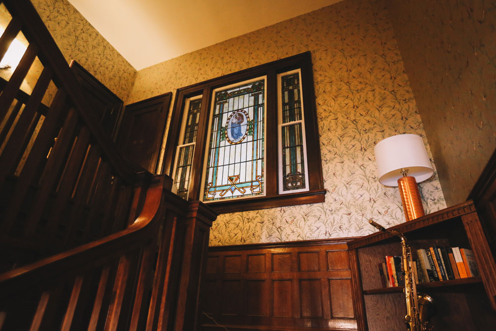 The stairs to our bedrooms, featuring an original stained-glass portrait of Pandora Fraser
