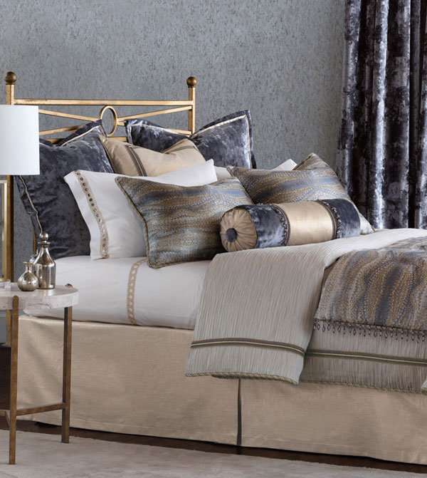 Imogen dazzles in the timeless appeal of precious metals. Its textured gray duvet cover and distressed-velvet Euro shams provide the perfect backdrop for its shimmering main fabric, a wavy and lustrous textile in a range of metallic and stony hues. Tassels and silvery-gold ruffles add an extra dimension of eye-catching and sophisticated luster.