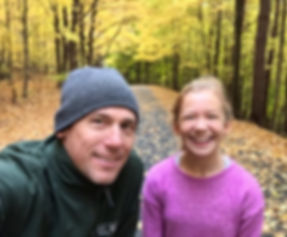 A smiling father and daughter in the woods
