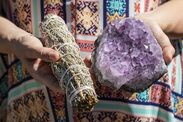 Woman holding sage and amethyst representing energy healing in hawaii.