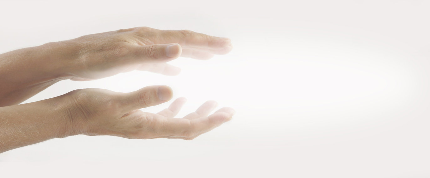 Hands with light symbolizing reiki healing in Hawaii.