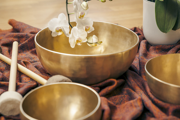 Singing bowl with orchids representing sound healing in Hawaii.