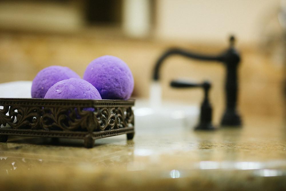 Purple bath bombs next to a tub, 50, fabulous & finally free