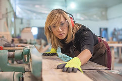 Female carpenter Using Electric Sander f
