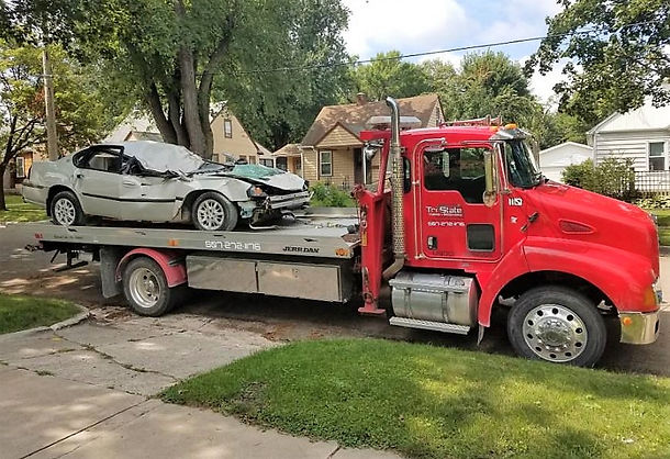 Totaled Vehicle after accident loaded onto Tri-State Towing & Recovery flatbed tow truck