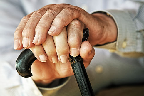 Old hands resting on a walking stick.jpg