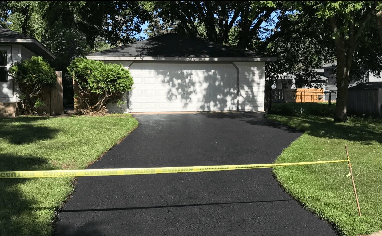 Freshly paved curved asphalt driveway