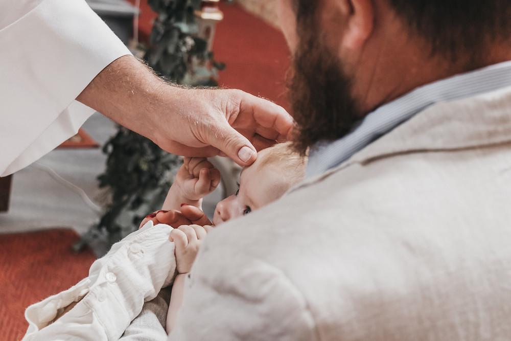 Levi wird getauft und bekommt das Kreuzzeichen auf die Stirn vom Langenloiser Pfarrer.