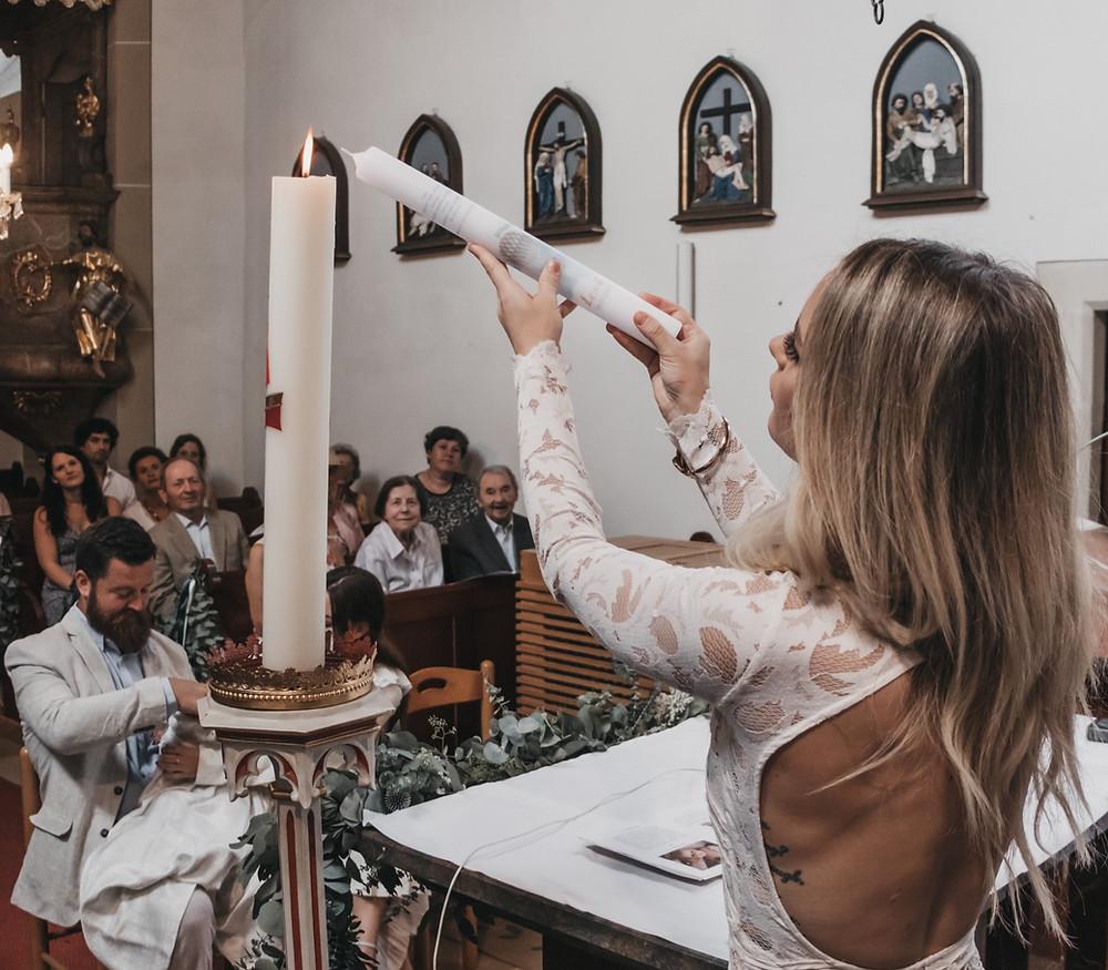 Taufpatin zündet Taufkerze in Kirche an