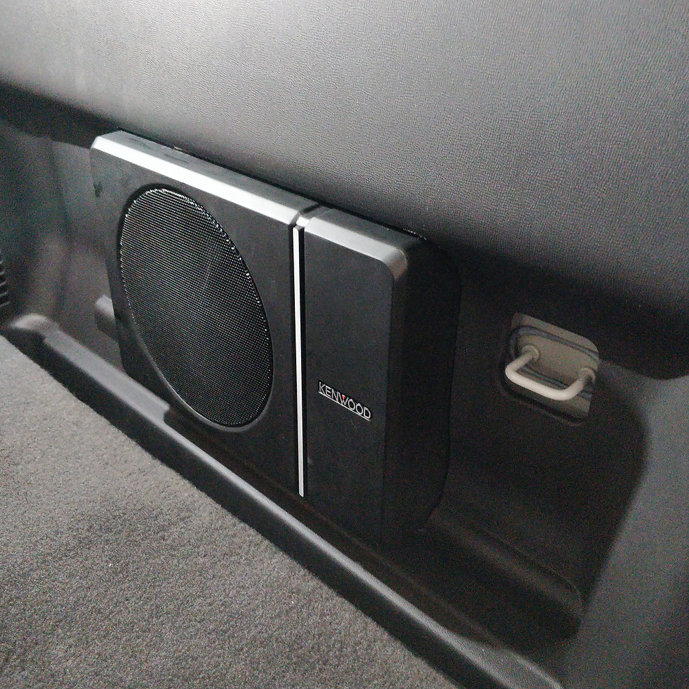 Kenwood Compact Powered Subwoofer mounted behind rear seat of dual cab ute.