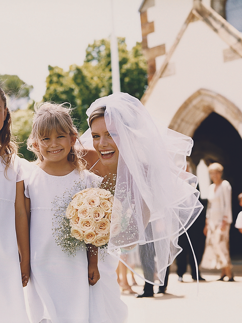 Bride smiling with flower girls