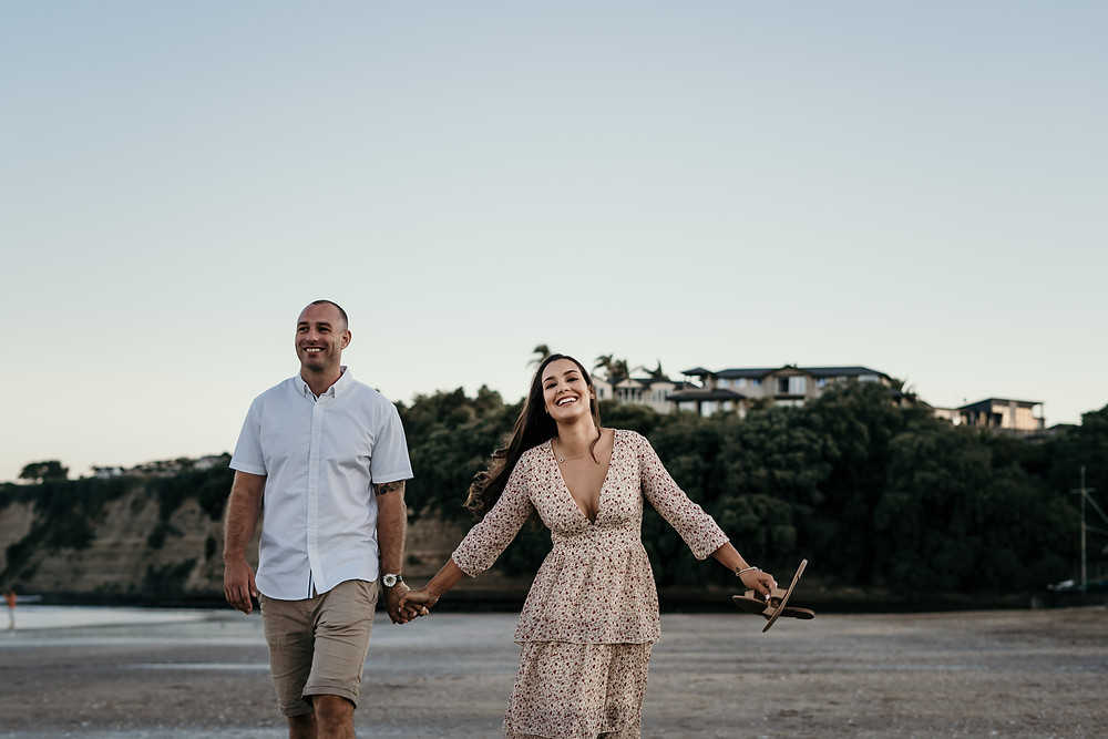 Engaged Couple holding hands Long Bay beach Auckland