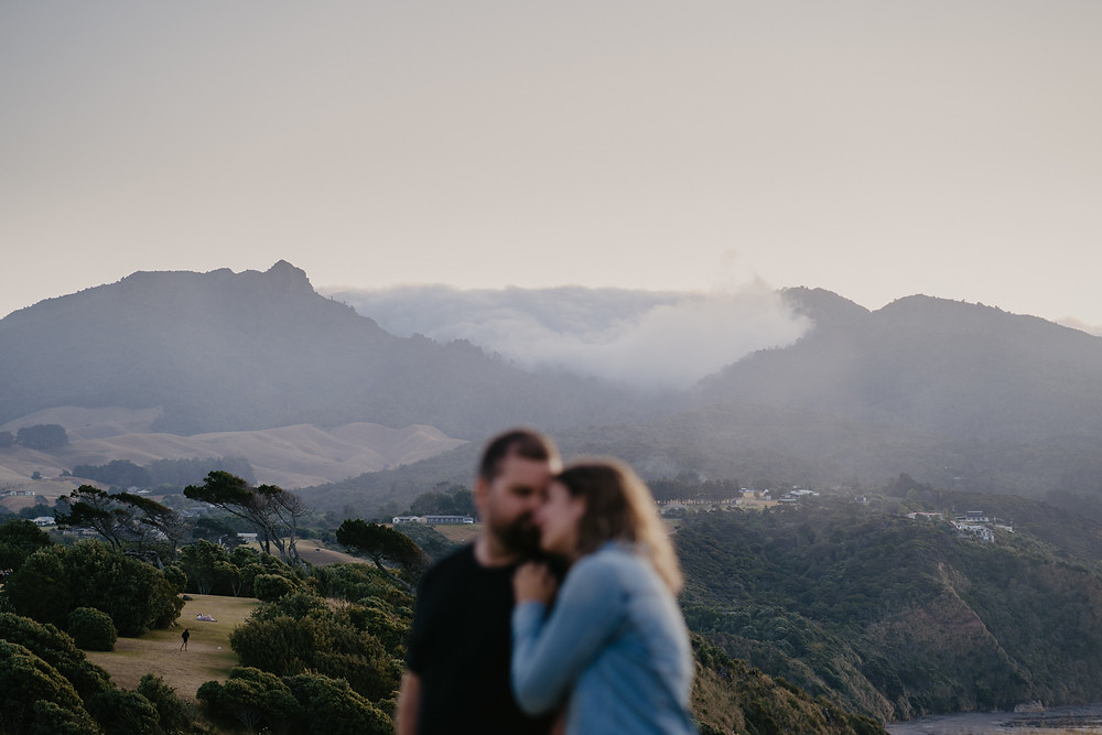 Engaged Couple hugging in Wainui Reserve Raglan New Zealand