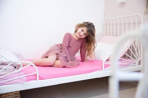 ילדה יושבת על ברולי עם כנפיים ורוד
