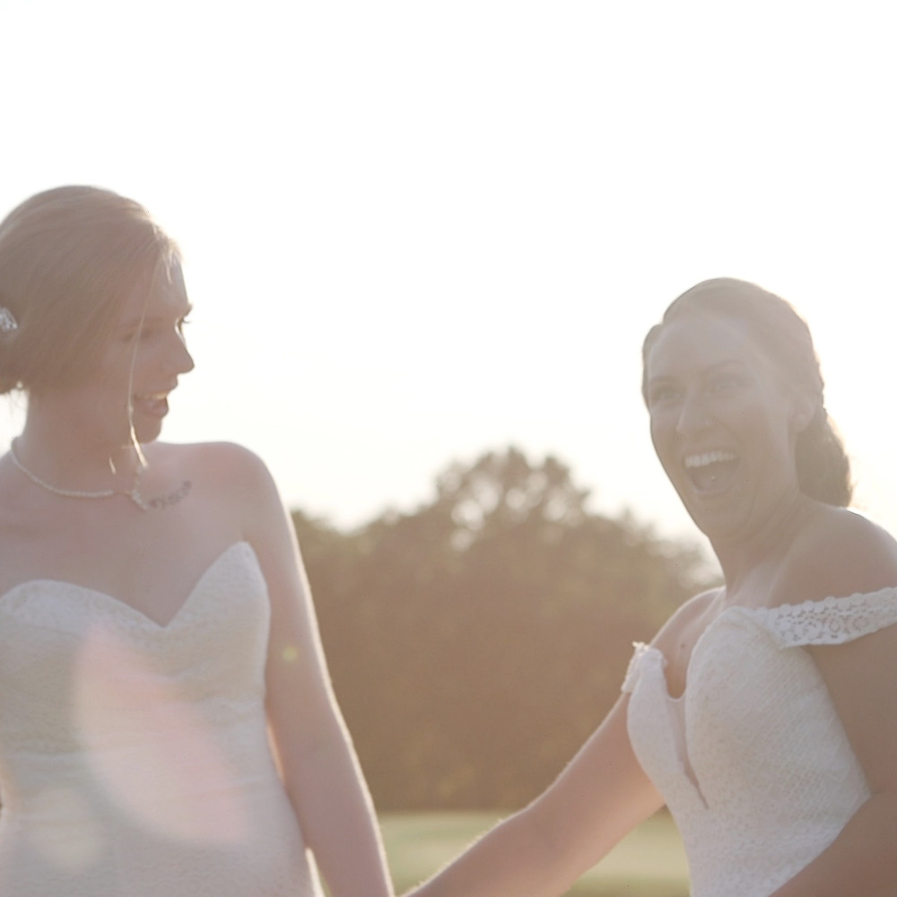 two brides laugh in a sunset