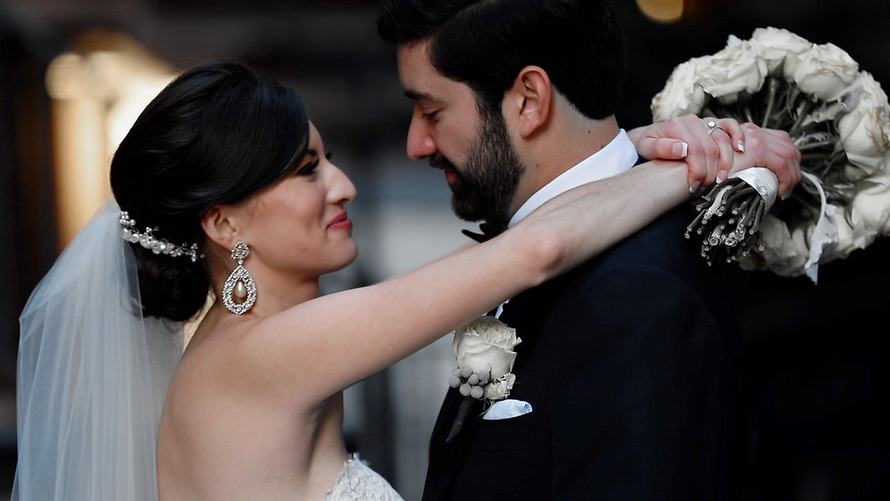 A bride with her arms around her groom after their wedding