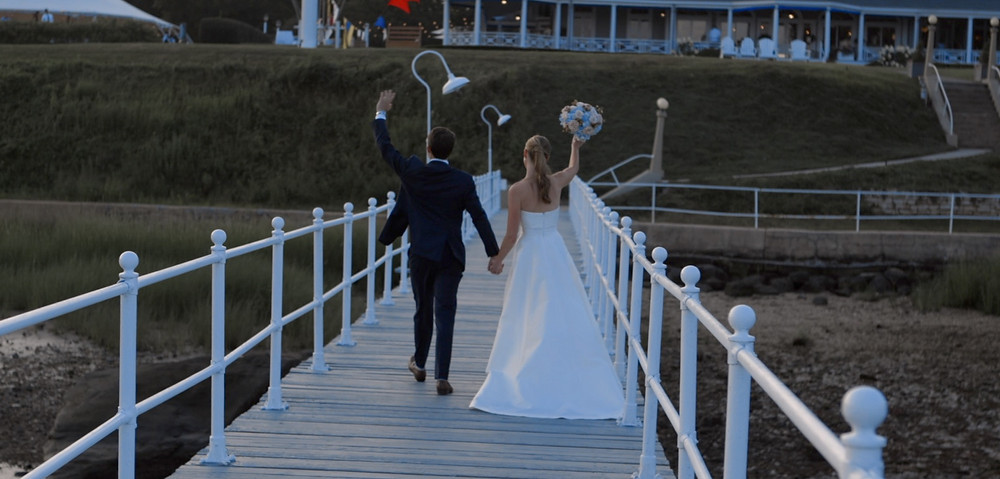 A bride and groom wave from a dock.