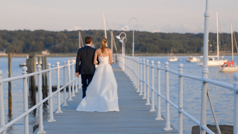A bride and groom walk toward the ocean