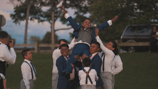 A groom is lifted by his groomsmen and brothers