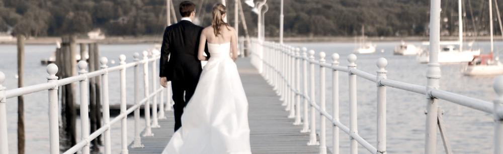 Wedding couple walks down a pier