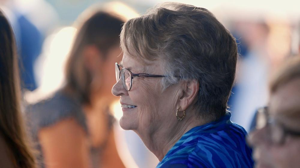 A grandma smiles at a wedding
