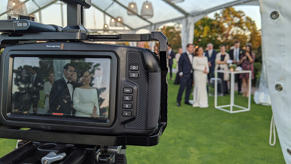 A couple in the distance, seen in close up on a nearby camera screen