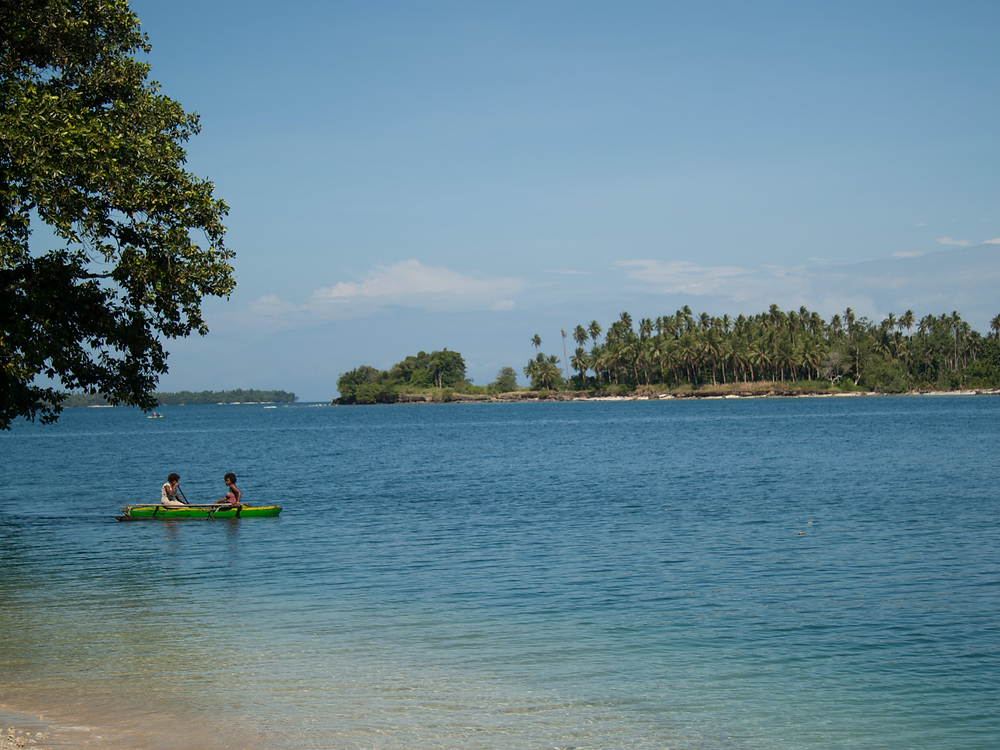 A picture of tropical waters, two people in a dugout canoe and tropical islands.