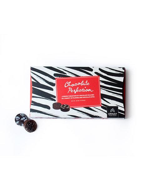 קופסה מלבנית בצבע שחור ולבן עם תווית אדומה ופרלינים להמחשה