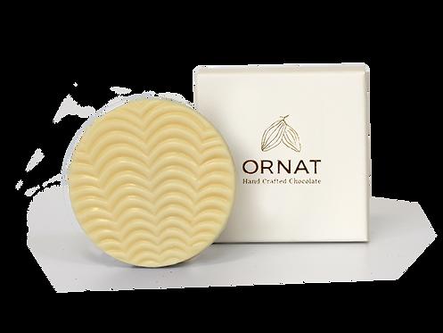 קופסה לבנה קטנה עם כיתוב לוגו החברה בצבע לבן  ודסקית עגולה משוקולד לבן עם חזית בצורת גלים