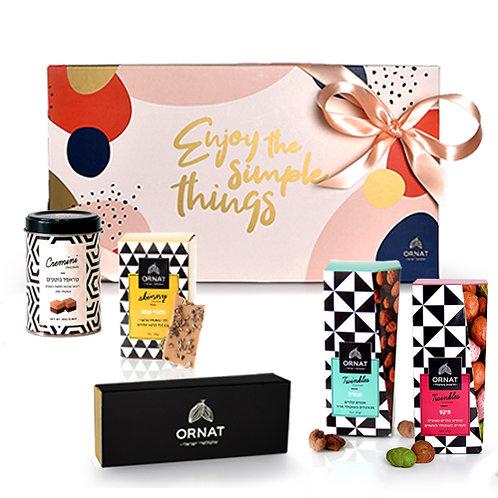 מארז מתנה גדול בצבע ורוד ושמנת עם תחתית בצבע אפור ארוז עם סרט בצבע ורוד בהיר עם מבחר מוצרי שוקולד