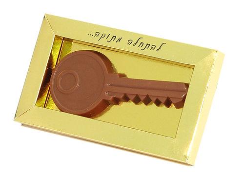 """קופסה בצבע זהב עם כיתוב """"להתחלה חדשה"""" עם שוקולד חלב בצורת מפתח"""