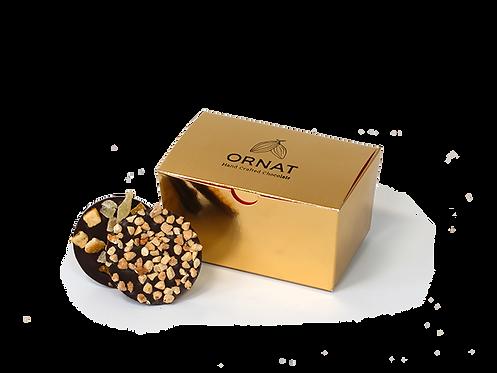 קופסה קטנה בצבע זהב עם חריטה בצבע שחור של לוגו החברה. מוצג עם שוקולד להמחשה