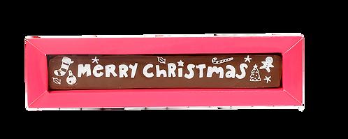 """קופסה ורודה ארוכה וצרה עם פרלין ארוך וצר משוקולד חלב ומעליו כיתוב בצבע לבן של """"Marry Cristmas"""""""