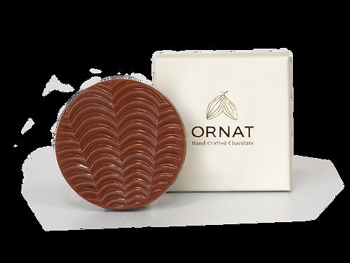 קופסה לבנה קטנה עם כיתוב לוגו החברה בצבע לבן ודסקית עגולה משוקולד חלב עם חזית בצורת גלים