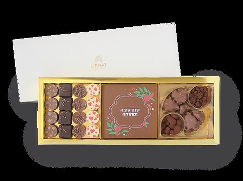 מארז צר וארוך עם תחתית בצבע זהב ומכסה לבן המחולק לשלושה תאים- מגוון שוקולדים,  לוחית  מרובעת משוקולד עם הדפס לחג ו16 פרלינים