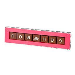 """""""קופסה צרה וארוכה בצבע ורוד עם משולשים שחורים ולבנים מכילה שבעה פרלינים משוקולד חלב עם כיתוב """"פסח שמח"""