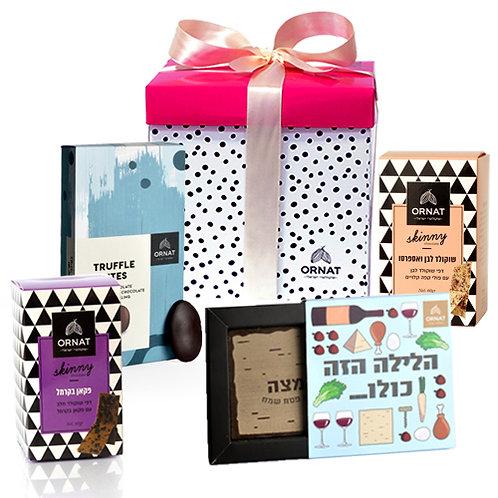 מארז בינוני בצורת קובייה. קופסה בצבע לבן עם עיטורי נקודות שחורות, מכסה בצבע ורוד וסרט בצבע ורוד בייבי. מכיל מבחר שוקולדים