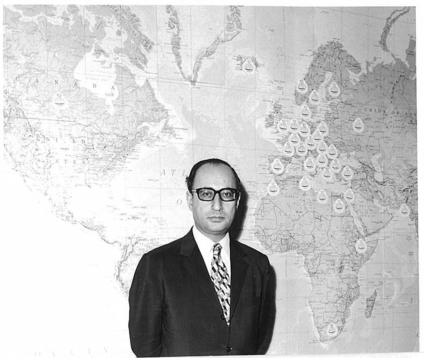 Shojāʿ al-Din Shafā, organizzatore delle Celebrazioni fin dal 1958, davanti ad una mappa dei Comitati Mondiali per le Celebrazioni