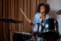 Black woman playing drum kit