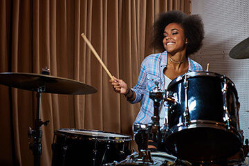 Black woman playing drum kit