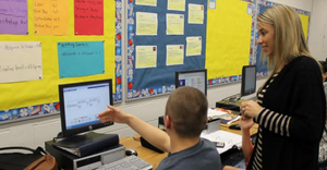 Lisa Floyd teaches computer science, coding and computational thinking with student by a computer.