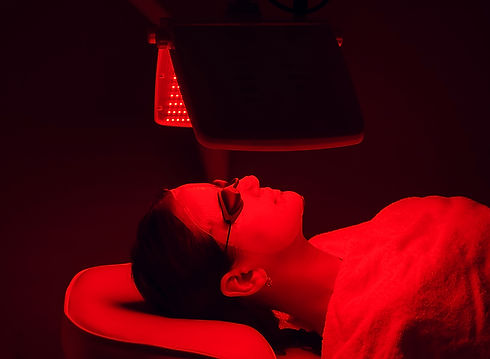 Young woman having red LED light facial therapy treatment in beauty salon. Beauty and well