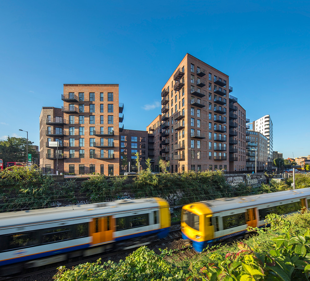 Tall brick clad wooden building with metro in front