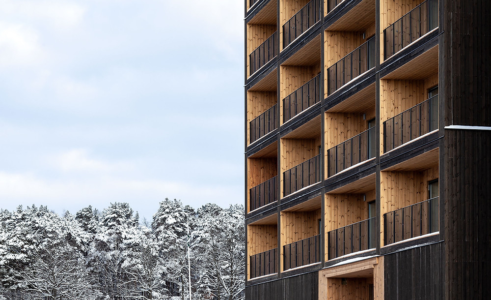 Tall wooden building with snow capped trees in the background