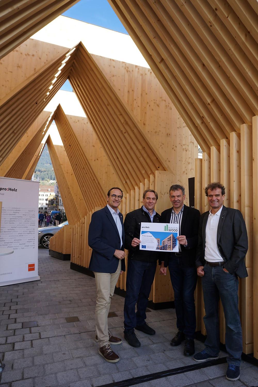 Politicians in front of tall wooden art installation in Innsbruck