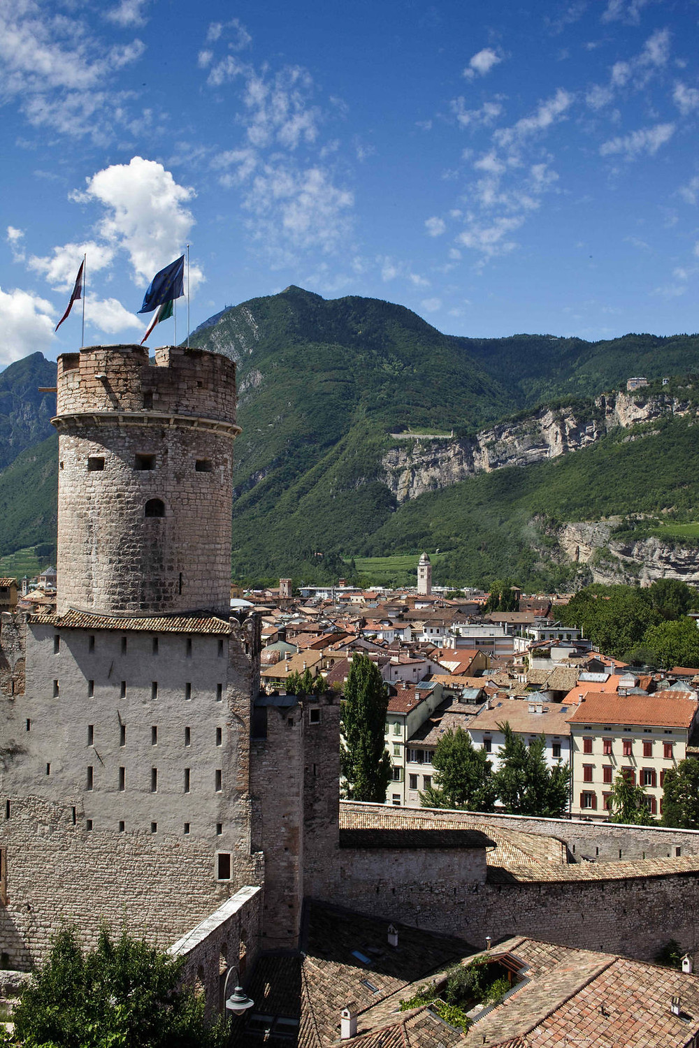 Trento Old Town, Castle Tower in front of old buildings and hills covered by forest